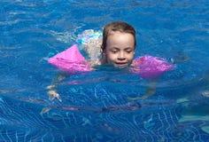 Natation joyeuse de petite fille dans le regroupement. Images stock
