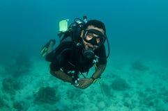 Natation mâle de plongeur autonome au-dessus de récif Photographie stock libre de droits