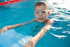 Natation positive de petit garçon avec le kickboard images stock