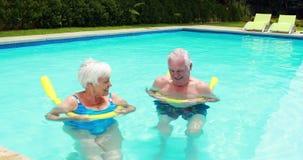 Natation supérieure de couples dans la piscine avec les tubes gonflables clips vidéos