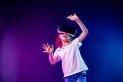 natation y de fille de 7 cours vieille O exp?rience du jeu de casque de VR sur le fond color? Enfant ? l'aide d'un instrument de  photographie stock libre de droits