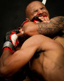 Nate Andrews locks in on his opponent. MMA Fighter Nate Andrews applies an arm lock on the head of his opponent and gets him to submit stock photography