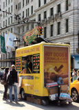 Nathan`s Hot Dog Vendor Near The Plaza Hotel, New York City, NYC, NY, USA. It is a beautiful, sunny day in New York City and here, tourists decide what to buy royalty free stock photo