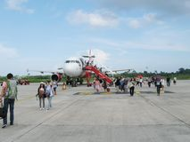 NATHON SI THAMMARAT, THAILAND - OCTOBER 18, 2013: Aircraft and passengers on airfield of airport. Royalty Free Stock Photography