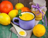 Natillas del limón y limones, naranjas y menta frescos en la tabla de madera vieja kurd Foto de archivo