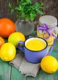 Natillas del limón y limones, naranjas y menta frescos en la tabla de madera vieja kurd Imagen de archivo