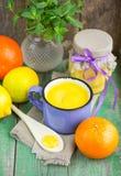 Natillas del limón y limones, naranjas y menta frescos en la tabla de madera vieja kurd Foto de archivo libre de regalías