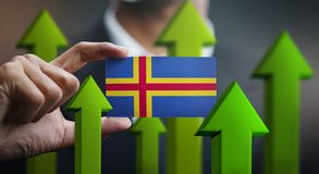 Nation Growth Concept, Green Up Arrows - Businessman Holding Car. D of Aland Islands Flag royalty free stock photo