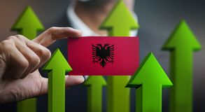 Nation Growth Concept, Green Up Arrows - Businessman Holding Car. D of Albania Flag royalty free stock photos