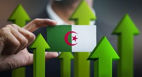 Nation Growth Concept, Green Up Arrows - Businessman Holding Car. D of Algeria Flag stock photography