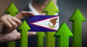 Nation Growth Concept, Green Up Arrows - Businessman Holding Car. D of American Samoa Flag stock photography