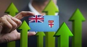 Nation Growth Concept, Green Up Arrows - Businessman Holding Car. D of Fiji Flag royalty free illustration