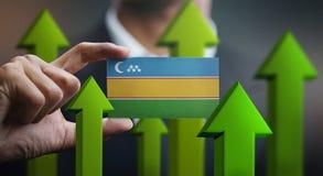 Nation Growth Concept, Green Up Arrows - Businessman Holding Car. D of Karakalpakstan Flag vector illustration