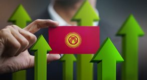 Nation Growth Concept, Green Up Arrows - Businessman Holding Car. D of Kyrgyzstan Flag royalty free illustration