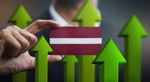 Nation Growth Concept, Green Up Arrows - Businessman Holding Car. D of Latvia Flag vector illustration