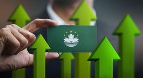 Nation Growth Concept, Green Up Arrows - Businessman Holding Car. D of Macau Flag stock illustration