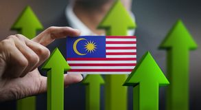 Nation Growth Concept, Green Up Arrows - Businessman Holding Car. D of Malaysia Flag royalty free illustration