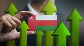 Nation Growth Concept, Green Up Arrows - Businessman Holding Car. D Oman Flag royalty free illustration