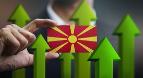 Nation Growth Concept, Green Up Arrows - Businessman Holding Car. D of Republic of Macedonia Flag royalty free illustration