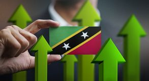 Nation Growth Concept, Green Up Arrows - Businessman Holding Car. D of Saint Kitts and Nevis Flag royalty free illustration