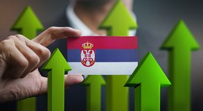 Nation Growth Concept, Green Up Arrows - Businessman Holding Car. D of Serbia Flag royalty free illustration
