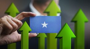 Nation Growth Concept, Green Up Arrows - Businessman Holding Car. D of Somalia Flag stock image