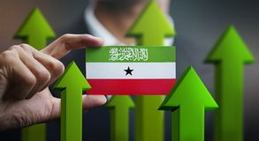Nation Growth Concept, Green Up Arrows - Businessman Holding Car. D of Somaliland Flag stock photo