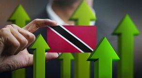 Nation Growth Concept, Green Up Arrows - Businessman Holding Car. D of Trinidad and Tobago Flag royalty free stock photos