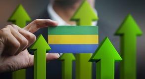 Nation Growth Concept, Green Up Arrows - Businessman Holding Car. D of Gabon Flag stock illustration