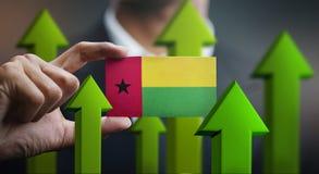 Nation Growth Concept, Green Up Arrows - Businessman Holding Car. D of Guinea-Bissau Flag stock illustration