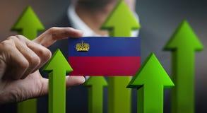 Nation Growth Concept, Green Up Arrows - Businessman Holding Car. D of Liechtenstein Flag vector illustration