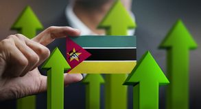 Nation Growth Concept, Green Up Arrows - Businessman Holding Car. D of Mozambique Flag vector illustration
