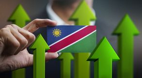 Nation Growth Concept, Green Up Arrows - Businessman Holding Car. D of Namibia Flag royalty free illustration