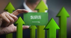 Nation Growth Concept, Green Up Arrows - Businessman Holding Car. D of Saudi Arabia Flag stock illustration