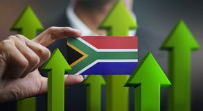 Nation Growth Concept, Green Up Arrows - Businessman Holding Car. D of South Africa Flag royalty free stock images