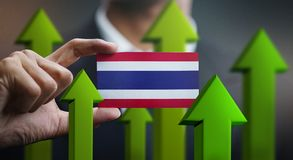 Nation Growth Concept, Green Up Arrows - Businessman Holding Car. D of Thailand Flag stock photo