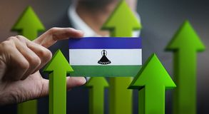 Nation Growth Concept, Green Up Arrows - Businessman Holding Car. D of Lesotho Flag stock illustration