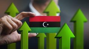 Nation Growth Concept, Green Up Arrows - Businessman Holding Car. D of Libya Flag stock illustration