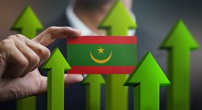 Nation Growth Concept, Green Up Arrows - Businessman Holding Car. D of Mauritania Flag royalty free illustration