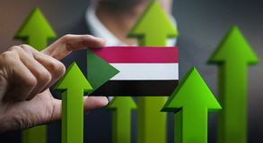 Nation Growth Concept, Green Up Arrows - Businessman Holding Car. D of Sudan Flag stock photography