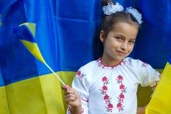 In nationaal kostuum tegen van Oekraïense vlag stock foto