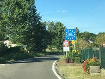 National border roadsign entering Federal Republic of Germany, with stars on blue as symbols for European Union member. Translation on white plate is Residents Stock Images