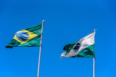 National brazilian flag and flag of Parana waving in the wind at flagpoles on the background of clear blue sky at sunny summer day. Brazil Royalty Free Stock Images