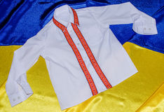 National clothes and flag. White shirt with embroidered ornament on background of the flag of Ukraine Royalty Free Stock Photography