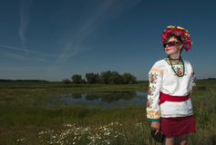 A girl in Ukrainian embroidery with a wreath on her head by the lake in a meadow among the flowers. National clothes - a girl in Ukrainian embroidery with a royalty free stock photos