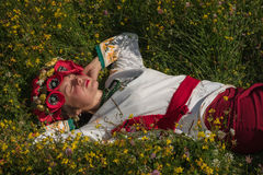 A girl in Ukrainian embroidery with a wreath on her head by the lake in a meadow among the flowers. National clothes - a girl in Ukrainian embroidery with a Stock Images