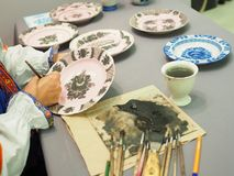 National craft. Woman paints a ceramic plate Stock Images