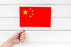 National day of China concept with flag in hand on white wooden background top view. Symbol of the national day of China concept with flag in hand on white royalty free stock photo