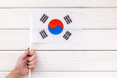National day of South Korea concept with flag in hand on white wooden background top view. Symbol of the national day of South Korea concept with flag in hand on stock photos