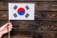 National day of South Korea concept with flag in hand on wooden background top view. Symbol of the national day of South Korea concept with flag in hand on stock photography